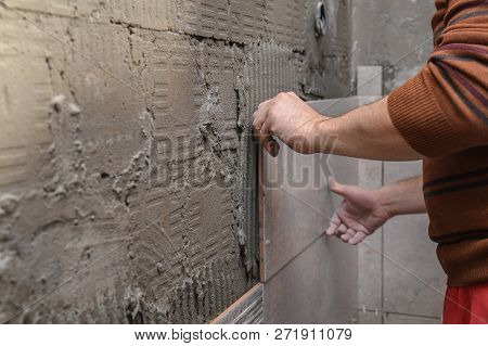 Gluing tiles on the wall. Laying tiles on the wall.  Worker installing big ceramic tiles on the walls stock photo