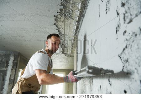 Plasterer using screeder spraying putty plaster mortar on wall stock photo