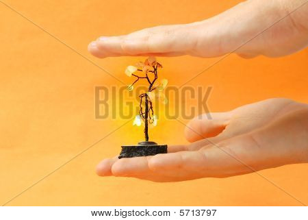 Hand with artificial metal tree. A symbol of happiness and fortune stock photo