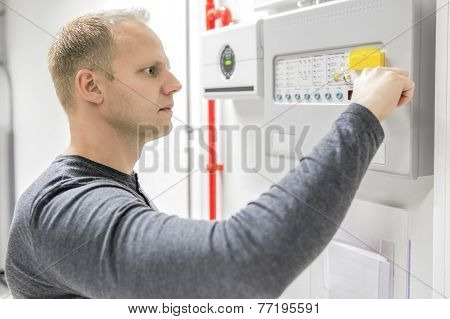 IT engineer or technician looking at alarm panel for aspirating fire detection system in datacenter. Inerte gass or nuvek gass system. stock photo