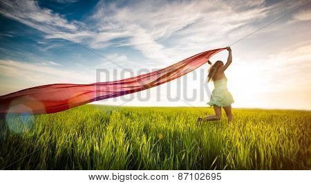 Young glad lady in wheat field with fabric. Summer way of life