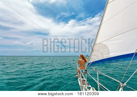 Joyful young woman portrait. Happy girl on board of sailing yacht have fun discovering islands in tropical sea on summer coastal cruise. Travel adventure yachting with kids on family vacation. stock photo