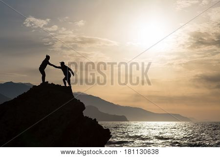 Teamwork couple helping hand trust help silhouette in mountains on sunrise. Team of climbers man and woman help each other on top of mountain climbing hiking together inspirational landscape.