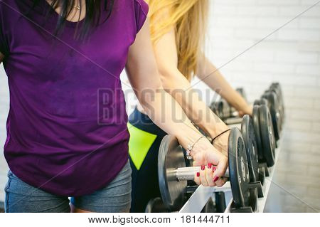 girl in a bright white gym. Two young athletic women near sports equipment are preparing for the traning with dumbbells holding up in their hands. Healthy way of life good spirits stock photo