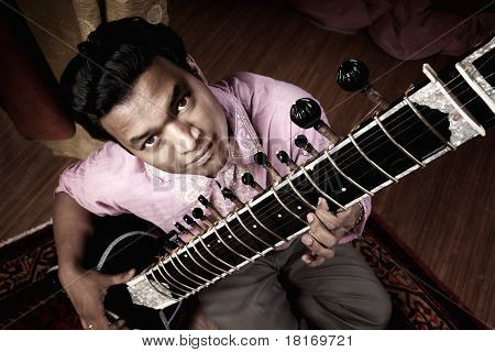 Birds-eye view of a hndsome young Indian man playing a sitar stock photo