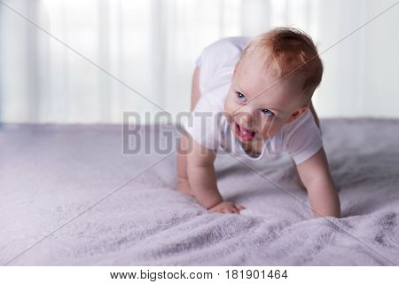 The boy with tongue hanging out doing his first steps. Open-eyed infant kid on the bed trying to toddle. Copy space. stock photo