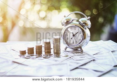 Close up of Business Finance and Money concept Save money for prepare in the future.time and money with green bokeh background e is money concept