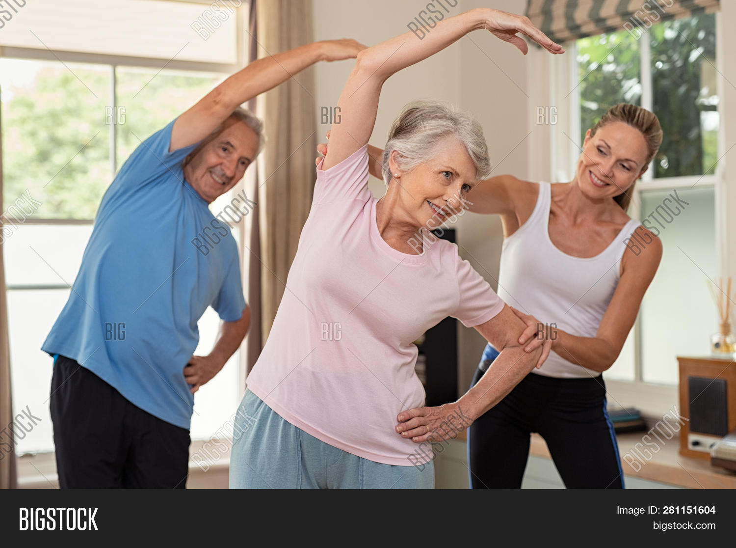 Senior couple doing exercise at home with physiotherapist. Mature gym trainer helping elderly man an