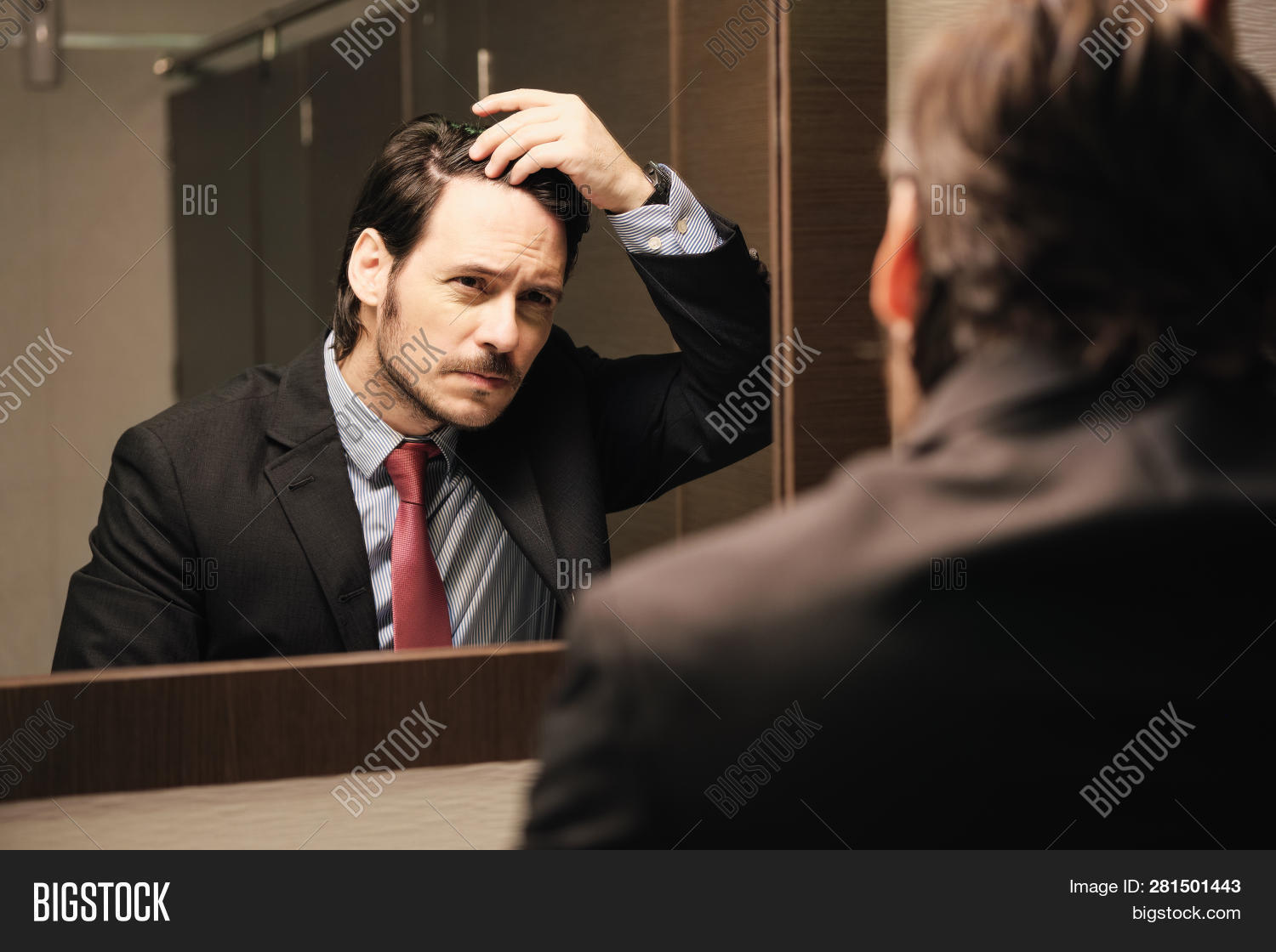Worried Hispanic Business Man Looking At Hairline In Office Restrooms