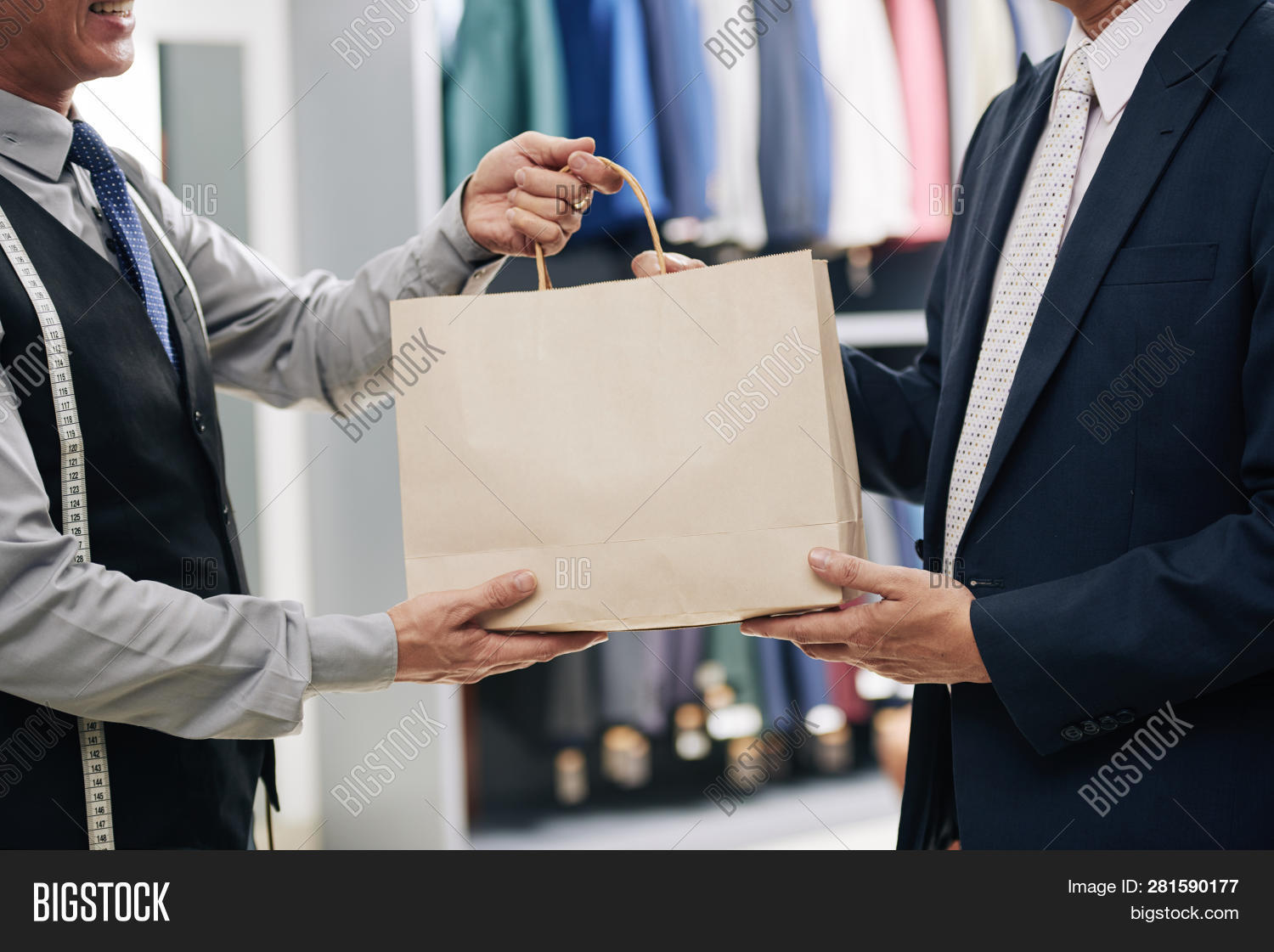 Man Receiving Paper-bag From Menswear Shop Assistant