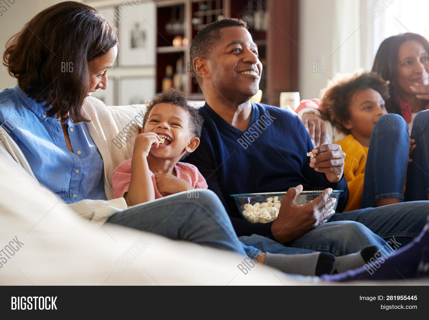 30s,50s,african american ethnicity,black,bonding,boy,brother,childhood,children,close up,copy space,daughter,day,domestic life,eating popcorn,entertainment,five people,free time,girl,grandfather,grandmother,happy,hispanic ethnicity,home,horizontal,indoors,kids,living room,low angle,man,middle aged,millennial,mixed race person,mother,multi-ethnic group,mum,parenthood,parents,pre-teen,selective focus,sister,sitting on sofa,son,three generation family,three quarter length,toddler,togetherness,watching movie,women,young adult