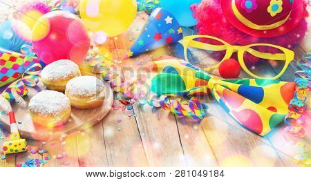 Colorful carnival or party background with donuts, balloons, streamers and confetti and funny face formed from wig, nose and glasses on rustic wooden planks with copy space stock photo