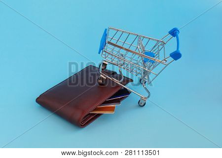 Shopping cart and credit cards in the wallet on blue background. Image use for online and offline shopping, marketing place world wide stock photo
