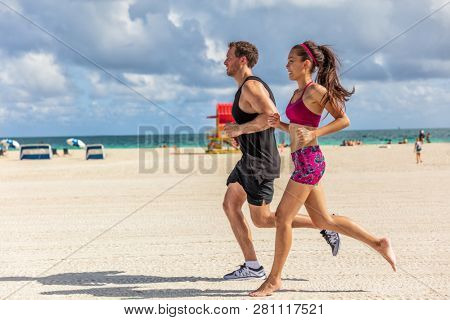 Running people jogging exercising on South Beach, Miami, Florida. Man and woman training partner runners working out together. Lifestyle active people. stock photo