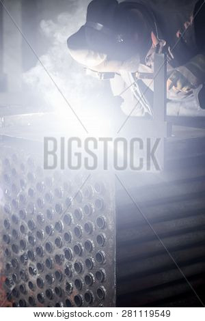Man welds metal. Worker welding steel in industry with safety mask safety gloves and safety equipment. Metal industry welding concept. stock photo