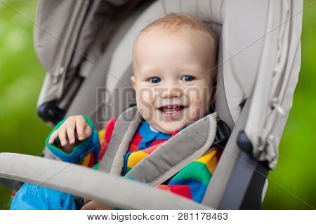 Baby boy in warm colorful knitted jacket sitting in modern stroller on a walk in a park. Child in buggy. Little kid in a pushchair. Traveling with young kids. Transportation for family with infant. stock photo