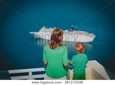 mother and little son looking at cruise ship at sea, Santorini, Greece stock photo