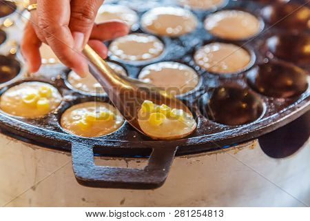 Khanom Khrok (coconut rice pancake), Traditional Thai Pudding Pancake Dessert, prepared by mixing rice flour, sugar, and coconut milk to form dough cooked in heating mantle (hot indented frying pan) stock photo