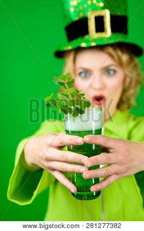 Patrick's green top hat. Saint Patrick's Day. Woman in green top hat holds glass with beer. Leprechaun. Green beer. Green hat with clover. Irish Traditions. Leprechaun costume. Pub. Selective focus. stock photo
