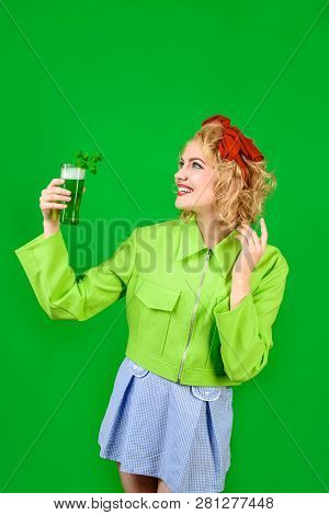 Saint Patrick's Day. Green top hat. St Patricks Day. Woman in top hat holds glass with green beer. Leprechaun. Green beer. Green hat with clover. Irish Traditions. Pub. Woman drinking in pub. stock photo