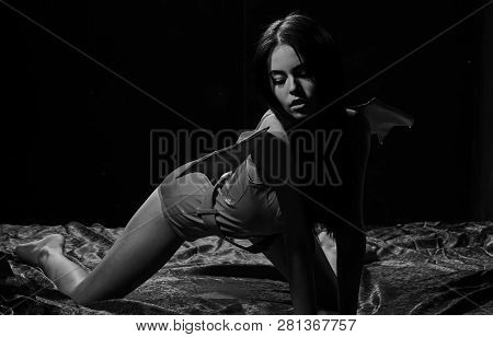 Demon concept. Woman on passionate face play role game. Girl sexy demon with wings, devil full of desire. Lady sexi dressed like demon, devil, black background. Demon sexy girl crawl on silk sheets stock photo
