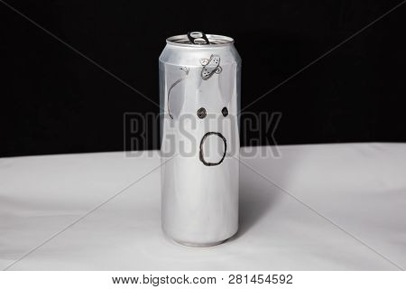 Concept of beaten man. Astonished emoticon on aluminium can, Emoji with surprised face. On black background stock photo