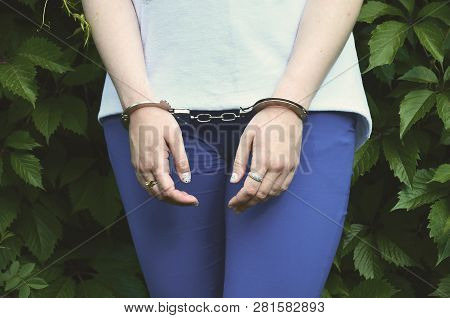 Fragment of a young criminal girls body with hands in handcuffs against a green blossoming ivy leaves background. The concept of detaining an offender of a female criminal in a rural environment stock photo