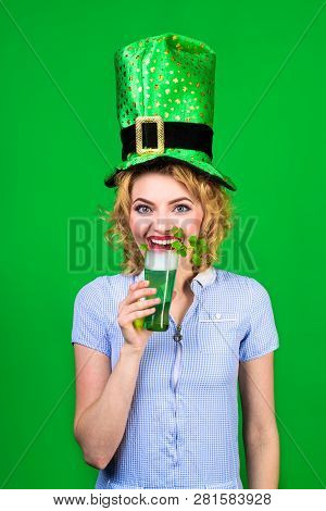 Saint Patrick's Day. Woman in top hat holds glass with green beer. St Patricks Day. Leprechaun. Green beer. Green top hat. Green hat with clover. Irish Traditions. Pub. Woman drinking in pub. stock photo