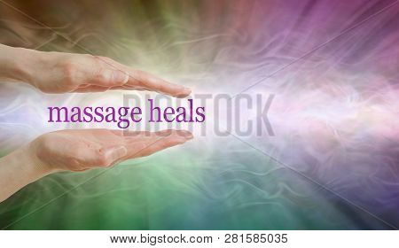Massage HEALS so give it a try - parallel hands with the words MASSAGE HEALS floating between against a radiating multicoloured ethereal energy background and copy space stock photo
