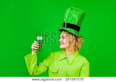 Saint Patrick's Day. Woman in top hat holds glass with green beer. St Patricks Day. Irish beer. Green beer. Green top hat. Green hat with clover. Irish Traditions. Pub. Woman drinking in pub. Isolated. stock photo