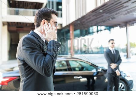 Confident secret service agent listening to updates from security earpiece while waiting by car stock photo