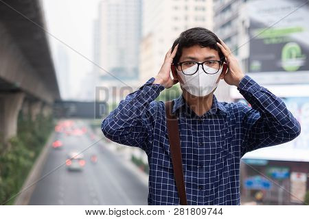 young Asian man wearing N95 respiratory mask protect and filter pm2.5 (particulate matter) against traffic and dust city. healthcare and air pollution concept stock photo