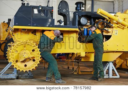 industrial worker during heavy industry machinery assembling on production line manufacturing workshop at factory stock photo
