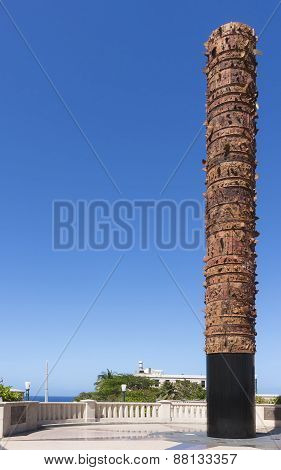 SAN JUAN PUERTO RICO - MARCH 6 2015: The Totem de Lurico Statue was erected to commemorate the 500th anniversary of the landing by Columbus in the Americas. The colomn looks over a public square under a blue sky. With its jagged edges and shards of cerami stock photo