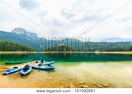Sea kayaks boats docked on the shore of Black Lake. Mountain landscape at cloudy daytime, Durmitor National Park, Zabljak, Montenegro. Beautiful nature. Summer recreations, travel and vacation.