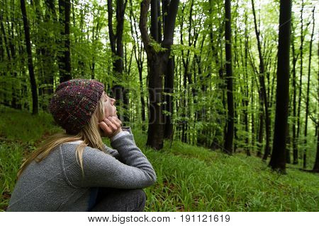 horizontal side view portrait of Caucasian young woman with long blonde hair and colorful wool hat leaning meditating with eyes closed in a green forest stock photo