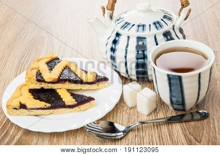 Pieces of bilberry pie in plate teapot cup of tea lumpy sugar and teaspoon on wooden table stock photo