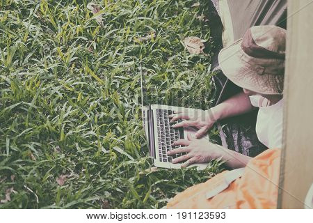 Young Man Tourist Lying And Using Laptop In Tent At Camping Site In Forest. Outdoor Activity In Summ