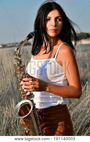 A young woman in a white T-shirt is standing in the field among the ears and holding a saxophone