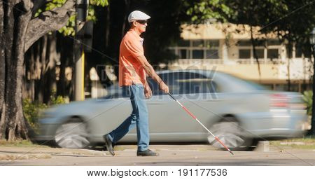 Hispanic blind man latino people with disability handicapped person and everyday life. Visually impaired man with walking stick crossing the street with cars and city traffic stock photo