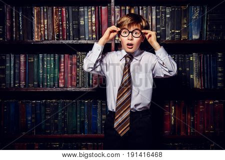 Surprised boy in glasses standing in the old library. Educational concept. stock photo