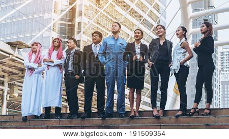 Multicultural business people group including Arabic East Asian Latin American standing in modern city. Concept of multi ethnic multiracial business team. stock photo