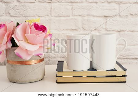 Two Mugs. White Mugs Mockup. Blank White Coffee Mug Mock Up. Styled Photography. Coffee Cup Product Display. Two Coffee Mugs On Striped Design Notebooks. Vase With Pink Roses stock photo