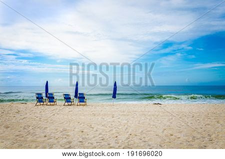 Tropical beach white sand and ocean, beach chairs and umbrellas.  Scenic travel destination location.