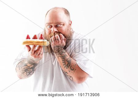 I want to eat it right now. Hungry male fatty is holding sweet cake and looking at it with appetite. He is standing and keeping fingers in mouth. Isolated and copy space stock photo