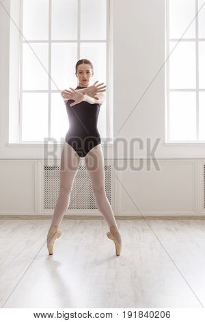 Classical Ballet dancer training. Beautiful graceful ballerina in black on pointe near large window in light hall.