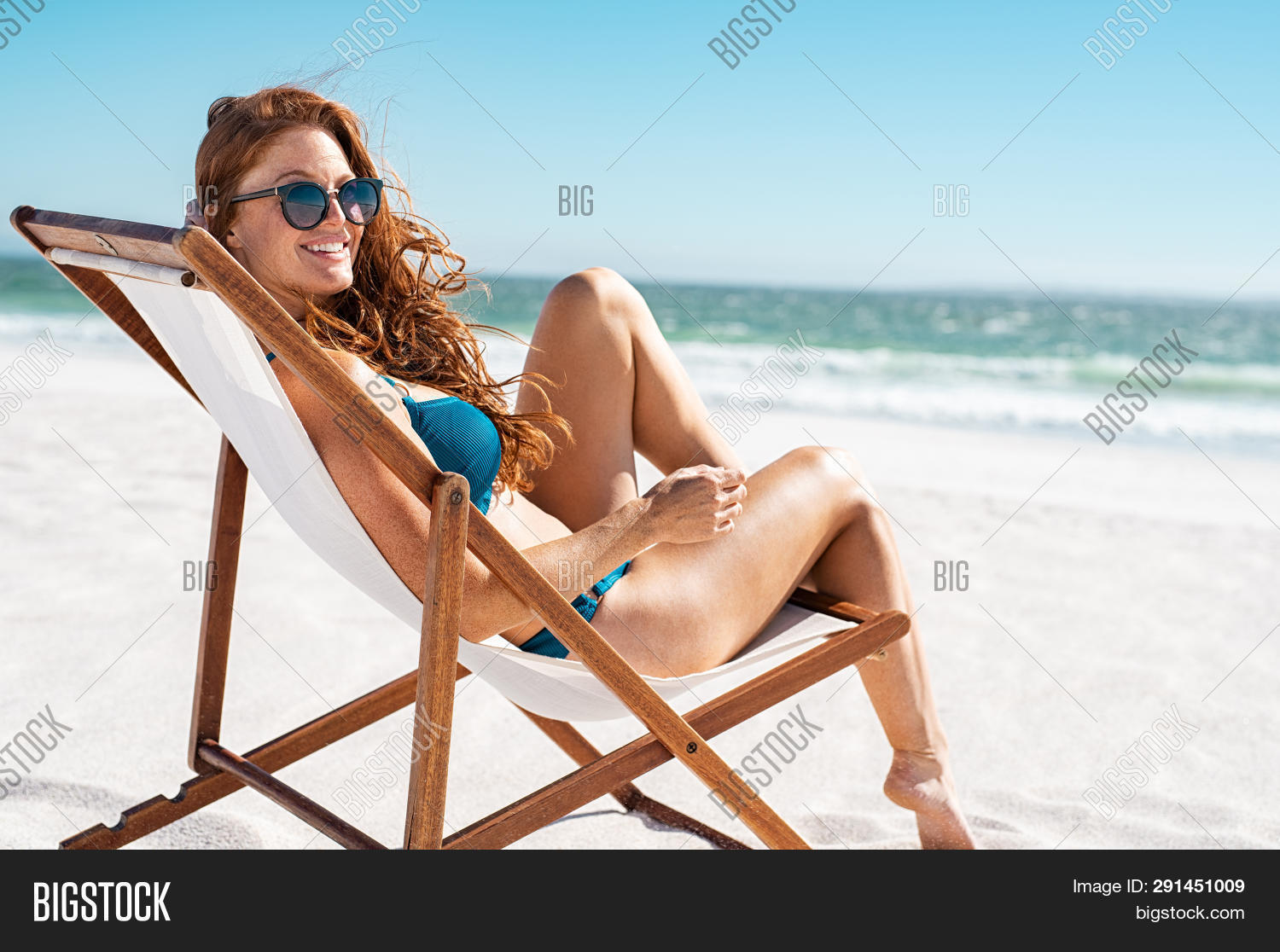Happy young woman relaxing on deck chair at beach while looking at camera. Mature woman with red hai
