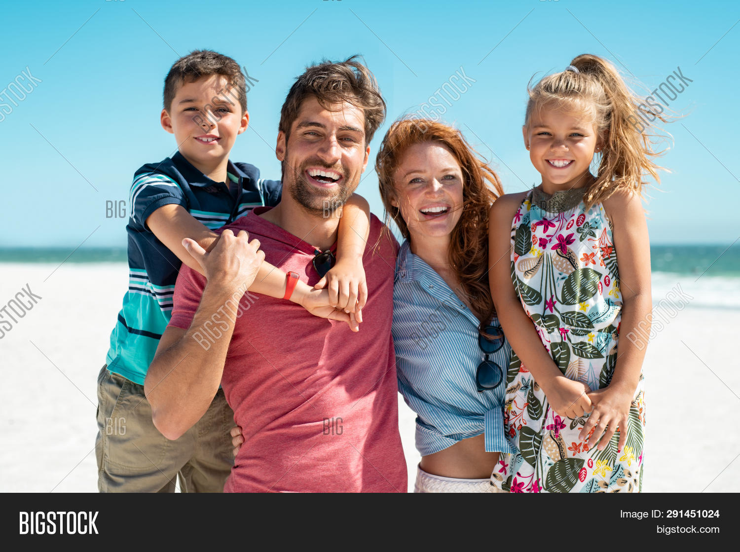 Portrait of happy family looking at camera at beach. Cheerful mother and father with cute daughter a