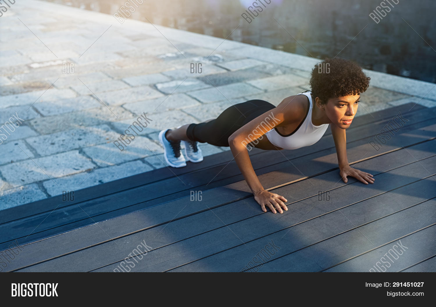 Fit african girl doing pushup exercise outdoor in the city street at dusk. Brazilian fitness woman w