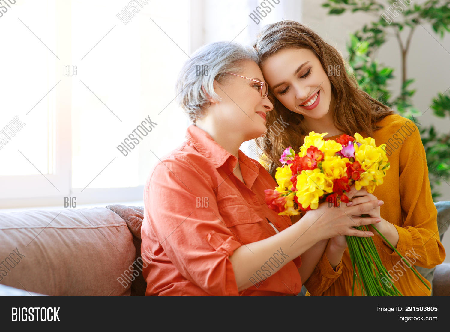 adult,beautiful,birthday,blonde,bouquet,care,caucasian,celebration,cheerful,child,daughter,day,elderly,face,family,female,flower,generation,gift,girl,giving,grandchild,granddaughter,grandmother,happy,holiday,home,kid,lifestyle,love,mature,mom,mother,old,older,parent,people,portrait,present,retired,senior,smile,smiling,sofa,surprise,together,two,white,woman,young